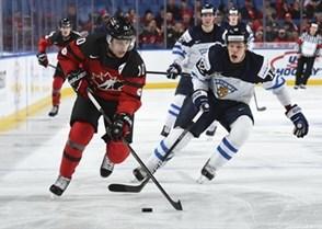 BUFFALO, NEW YORK - DECEMBER 26: Canada's Kale Clague #10 skates with the puck while Finland's Otto Koivula #12 chases him down during preliminary round action at the 2018 IIHF World Junior Championship. (Photo by Matt Zambonin/HHOF-IIHF Images)